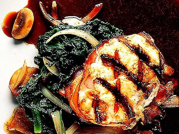 Baconlindad marulksmedaljong på spenatbädd med spegel av rödvinssås