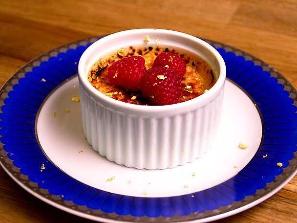 Crème brûlée med guldkant och färska bär