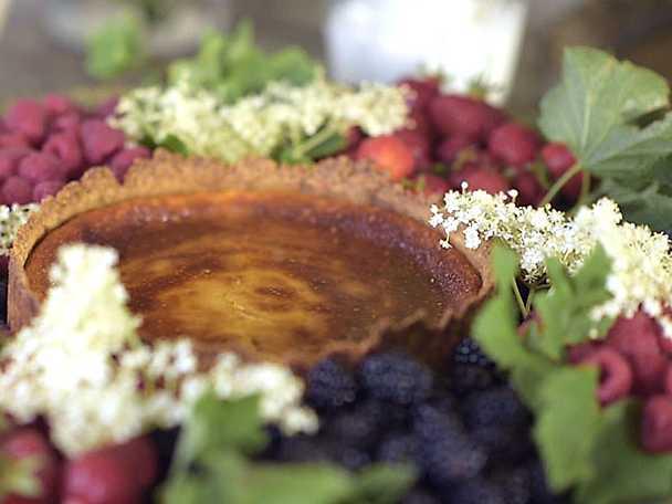färskosttårta med flädergelé, färska bär och grädde