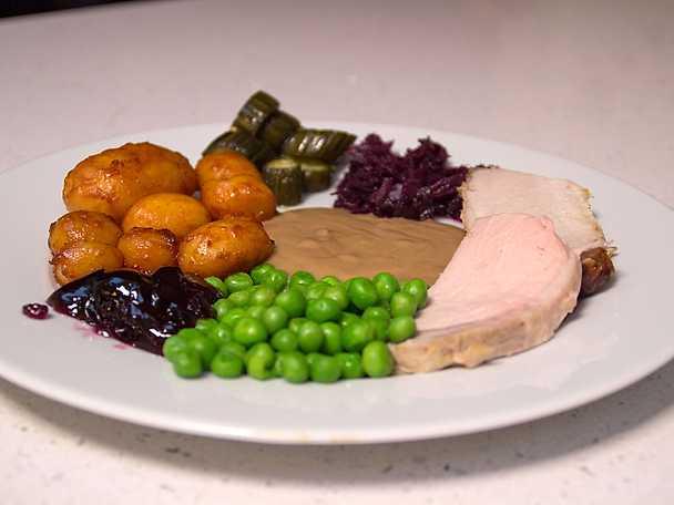 Flæskesteg med brunede kartofler, rødkål og brun sovs