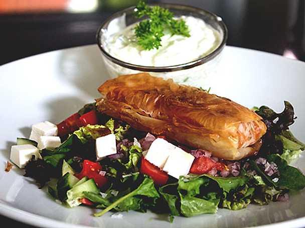 Köttfärs- och grönsaksfylld filodeg på salladsbädd med tsatsiki