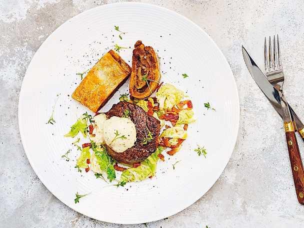 Oxfilé med baconstekt savoykål, smördegsinbakad potatis och senapsgrädde