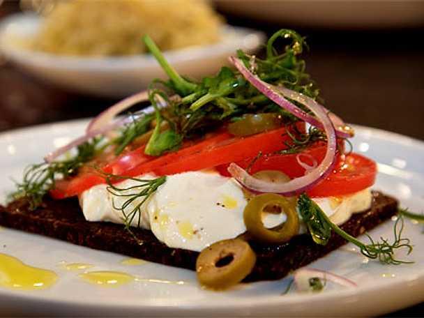 Pumpernickelsmörgås med sallad på tomat, rödlök, oliver och ärtskott
