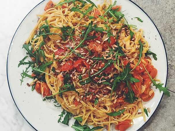 Smörig linguine med färska tomater, vitlök, solrosfrön och ruccola