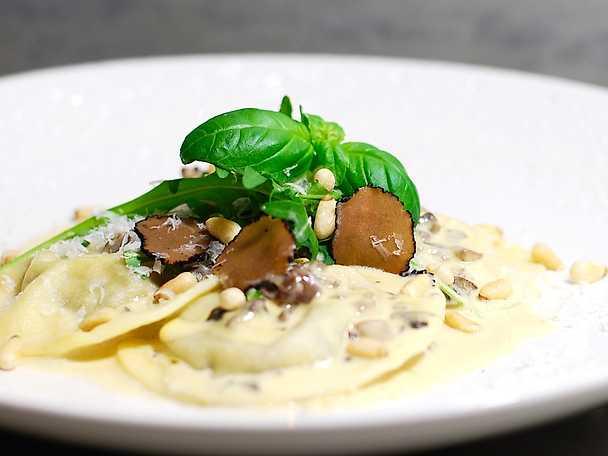 Svampravioli med krämig vitvinssås, rostade pinjenötter, ruccola och svart tryffel